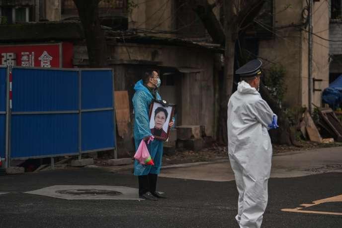 Un proche tient le portrait d'une victime du Covid-19 prèsdu cimetière Biandanshan à Wuhan dans la province du Hubei en Chine, le 31 mars.