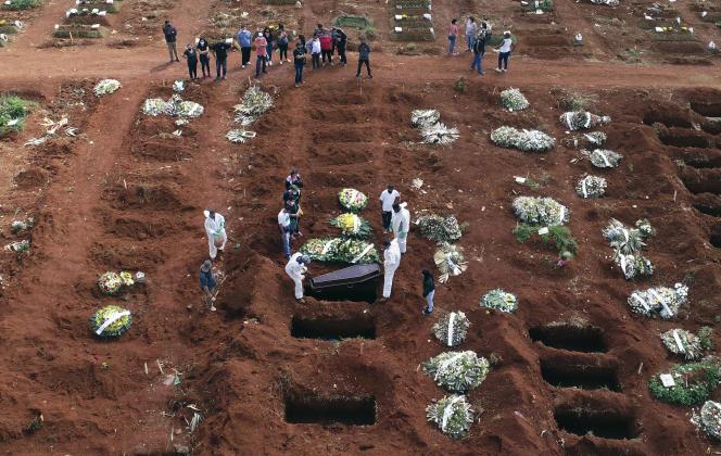 Des employés ducimetière de Vila Formosa, à Sao Paulo, enterrent une personne morte suite à des complications du Covid-19, le 7 avril.